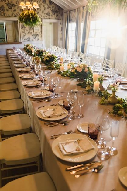 カトラリーがエレガントに配置された美しいセンターピースを備えた細長いテーブル Premium写真