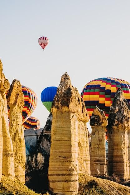 カッパドキアの上を飛んで、トゥルキアのスローガンと色とりどりの熱気球の詳細。 Premium写真