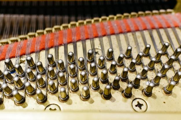 Деталь интерьера рояля с деки, струн и булавок. Premium Фотографии