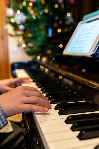 クリスマスの間に子供の手がピアノの鍵を弾きます。 Premium写真