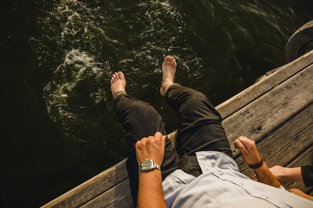 海の水で彼の足をさわやかな男性の観光客は、穀物フィルムを追加しました。 Premium写真