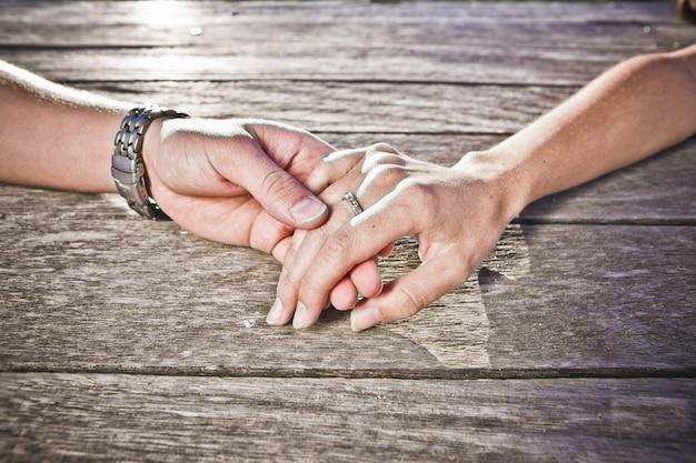 男と女の愛情を込めて木の上に横たわる自分の手を愛撫 Premium写真