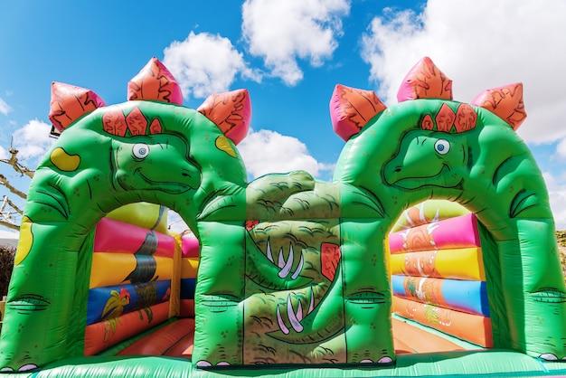 屋外の子供の遊び場で恐竜の形をした弾力のある城。 Premium写真