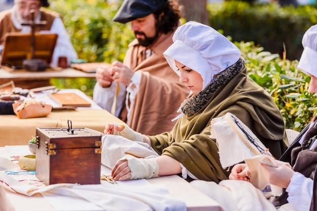 職人は中世の時代に偽装して、祭りの展示会で古い工芸品を見せました。 Premium写真