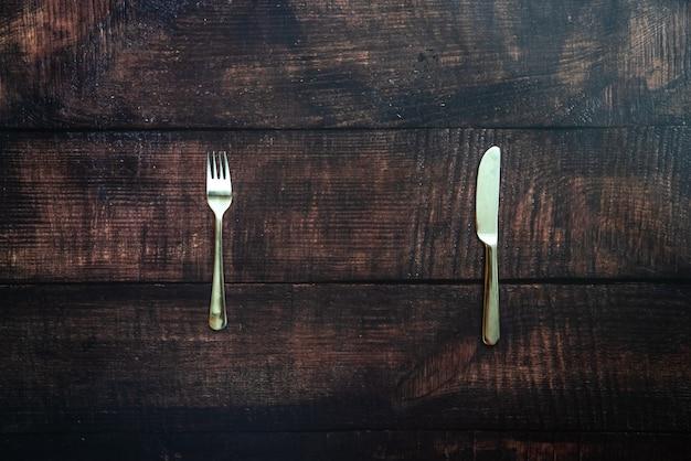 行方不明の食べ物の皿を待っているフォークとナイフで古い木製のテーブル Premium写真