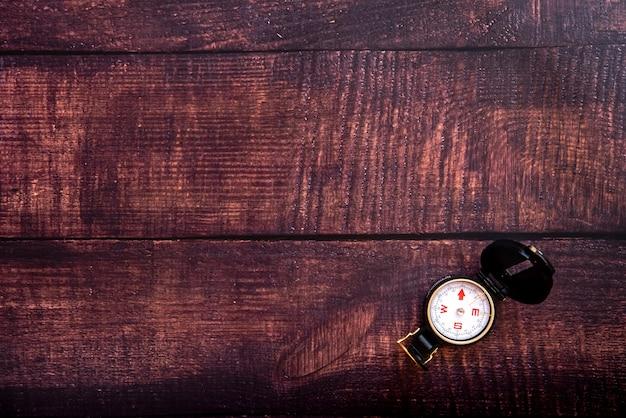 茶色の高齢者の木製テーブルの上の孤立したコンパス Premium写真