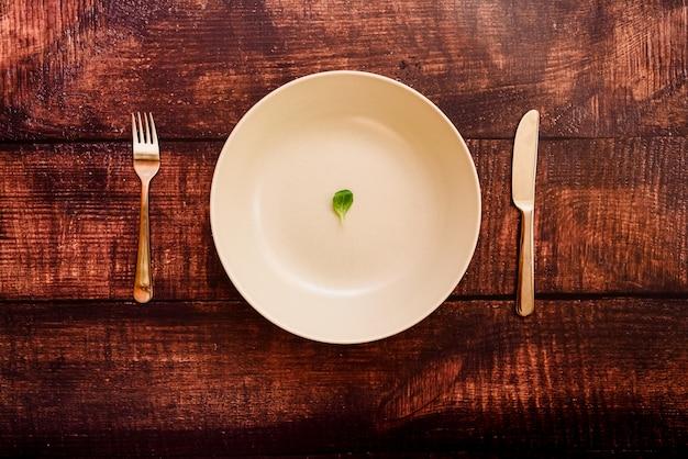 少量の野菜と一緒にダイエット、プレートとカトラリーのイメージ。 Premium写真