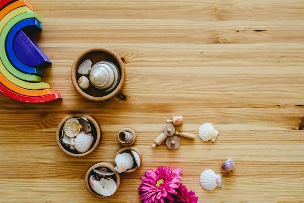 海の貝殻と紫の花でいっぱいの丸い木製の鉢のグループ Premium写真