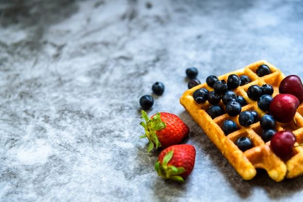 健康的な食品や抗酸化果物のための否定的なスペース、そしてジャンクフードとしてのワッフルのきれいな背景 Premium写真