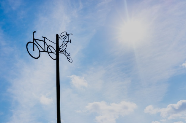 Скульптура с силуэтами велосипедов, висит на шесте, с неба и солнца на заднем плане. Premium Фотографии