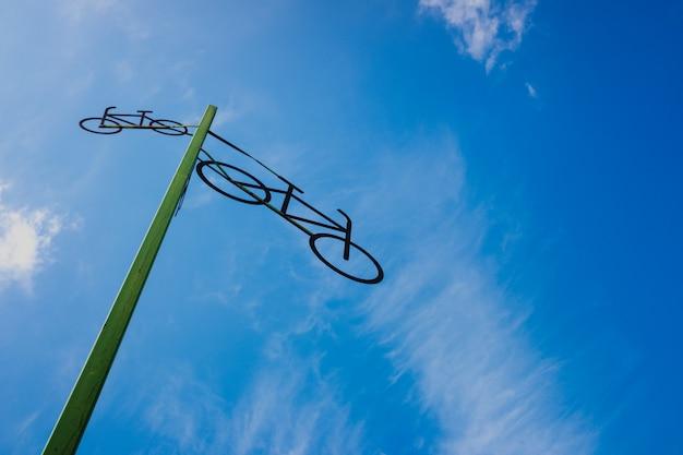 青い空と雲を背景に、道路を示す自転車の姿で投稿してください。 Premium写真