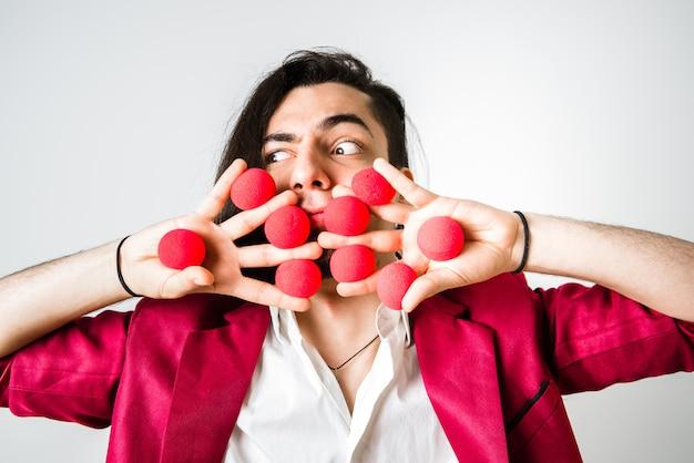 Маг с красными шариками в вытянутых руках. Premium Фотографии