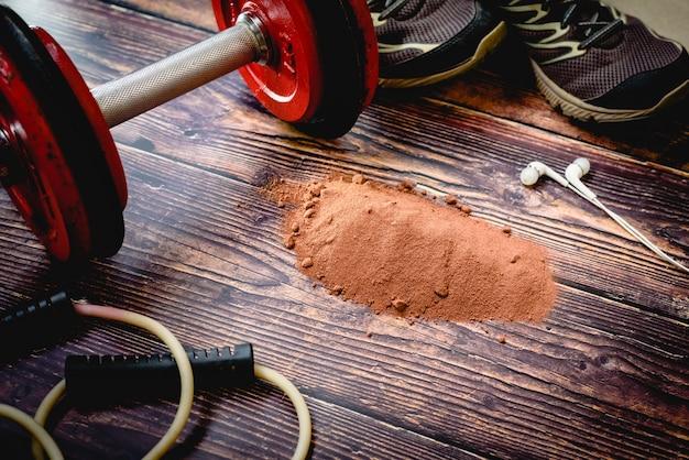ワークアウト中にジムの床にココアプロテインのホエイサプリメントパウダー。 Premium写真