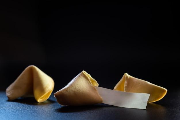 テキストの空スペースで黒の背景に分離された幸運のメッセージで壊れたラッキークッキー。 Premium写真