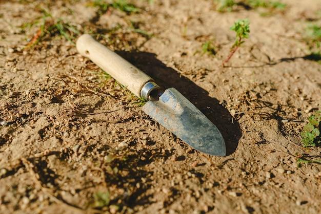太陽の下で庭の地面に捨てられた小さな庭のシャベル。 Premium写真