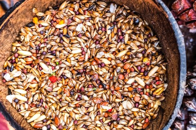 キビとバードシードの種子を持つ鳥の餌箱の詳細。 Premium写真