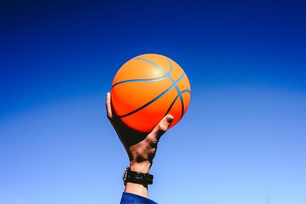 青い空、プレイへの招待、コピースペースのない領域にオレンジのバスケットボールを持っている手。 Premium写真