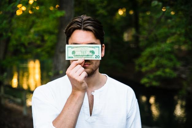 男はドル紙幣を保持し、資本主義によって彼の人格を検閲する彼の顔を隠しています。 Premium写真