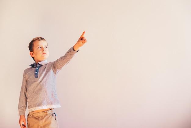 上げられた手と指が上向き、空白で指している子。 Premium写真