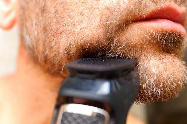 Мужчина бреет бороду с помощью электрической бритвы. Premium Фотографии