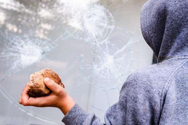 子供は石を手に持ってガラスにぶつけて窓を割る。 Premium写真