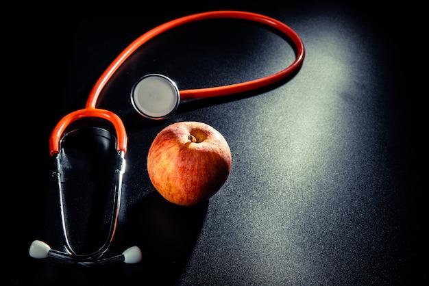 Черный фон с яблоком и стетоскопом Premium Фотографии