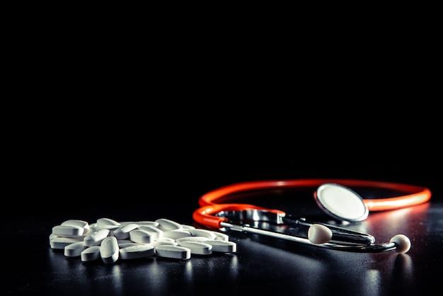 Черный фон с стетоскоп, здоровое питание избегает приема лекарств. Premium Фотографии