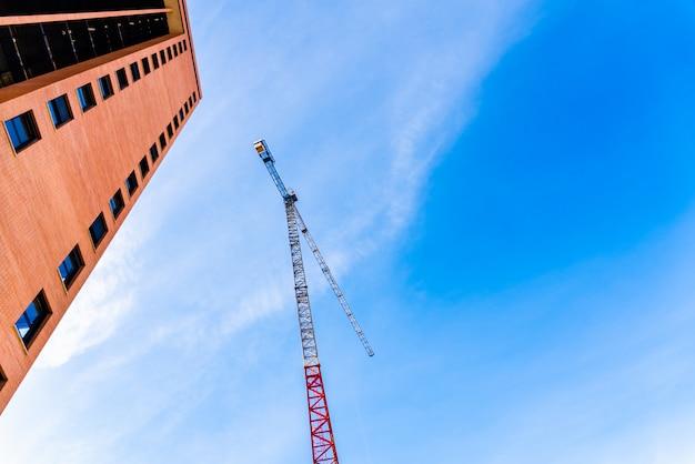住宅建設会社は、大型クレーンを設置して家を建て、実在の専門家によって販売されています。 Premium写真