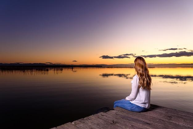 Женщина спокойно думает в красивом осеннем пейзаже на закате с теплыми тонами Premium Фотографии