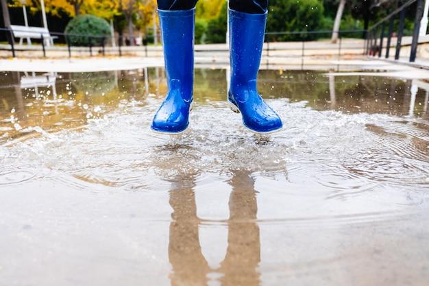 青い水ブーツを持つ少年は、水たまりにジャンプします。 Premium写真