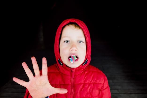 Страшный мальчик с красным капюшоном, освещенным неонами, - странная поза во время еды конфеты. Premium Фотографии