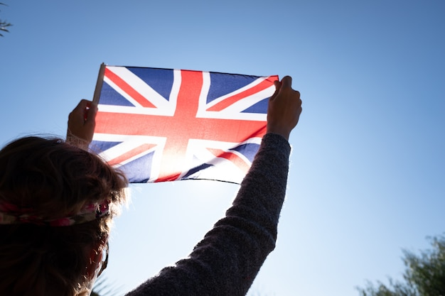 女性は愛国的な瞬間に太陽に対してイギリスの旗を保持しています。 Premium写真
