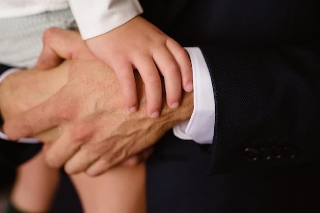 Конец-вверх рук ребенка отдыхая на кулаках его отца. Premium Фотографии