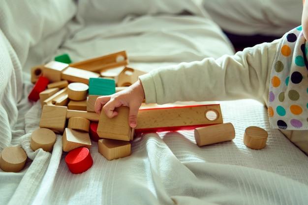 Малышка весело подбирает деревянные кубики, чтобы поиграть с ними и развить их пространственные чувства. Premium Фотографии