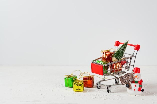 ミニクリスマスツリー、ギフトボックス、雪だるまとショッピングカート Premium写真