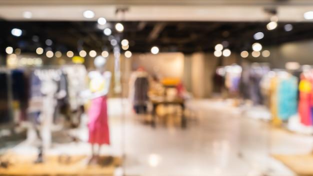 背景、服のショッピングコンセプトのショッピングモールで抽象的なぼやけた現代ファッション服店。 Premium写真
