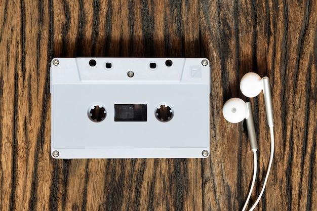 グランジビンテージウッドの背景、上面にイヤホンでレトロな古いオーディオカセットテープのオーバーヘッドショット Premium写真