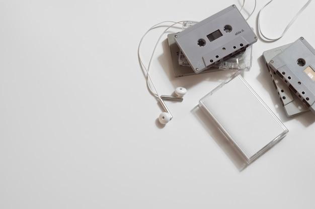 白い背景の上のイヤホンとレトロな古いオーディオカセットテープのオーバーヘッドショット、フラットコピースペース平面図を置きます。 Premium写真