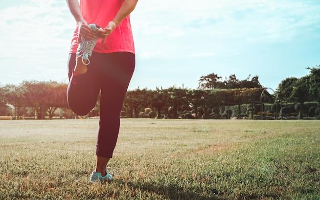 足のストレッチ体操をしている女性。 Premium写真