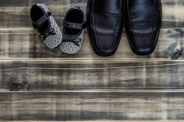 パパの黒のビジネスシューズと黒と白の子供スニーカーグランジさびた木材、家族の概念、ひとり親と父の日、コピースペースと平面図フラット横たわっていた。 Premium写真