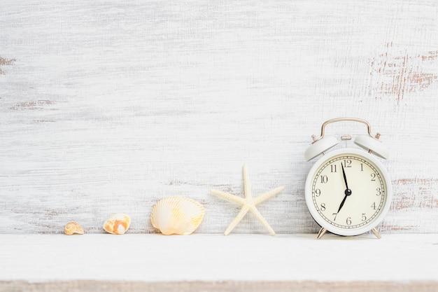 ヒトデ、さびた木材の白い背景の海の貝と白い目覚まし時計。夏の休日休暇、海ビーチ旅行休暇時間の背景概念。 Premium写真