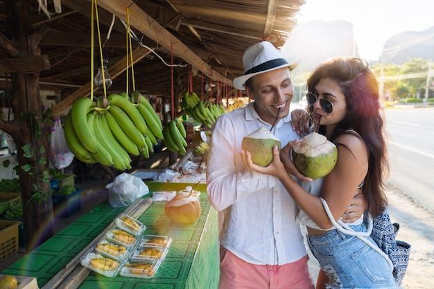 Молодая пара пьет кокосовые орехи на уличном рынке таиланда, туристы мужчина и женщина в традиции Premium Фотографии