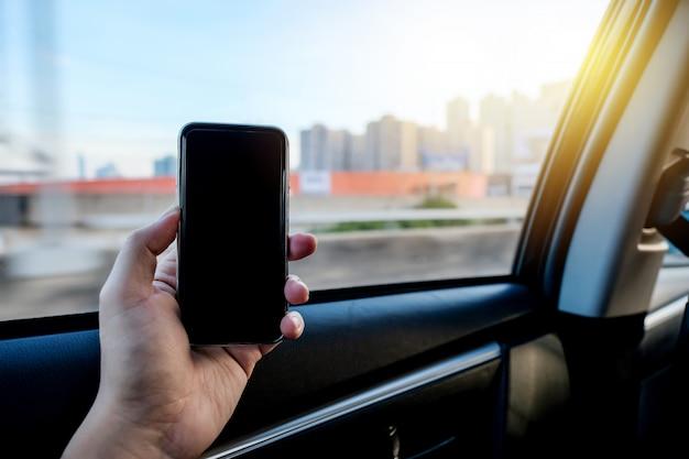 Рука захватывает смартфон, чтобы использовать мобильное приложение на заднем сиденье автомобиля такси. Premium Фотографии