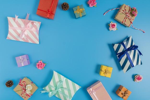 さまざまなギフトボックス、小さなピンクのバラと青の背景に松ぼっくり Premium写真