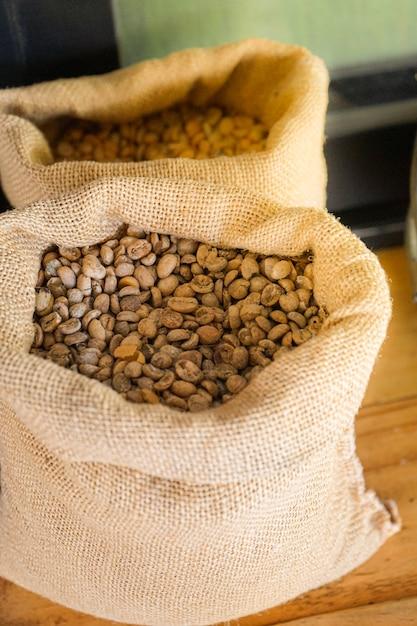 木製のテーブルに置かれた袋に生または未焙煎のコーヒー豆 Premium写真