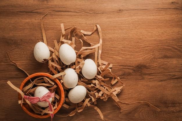 Пасха, связанное яйцо с красной лентой в деревянной миске и белые яйца на коричневой бумаге на деревянный стол Premium Фотографии