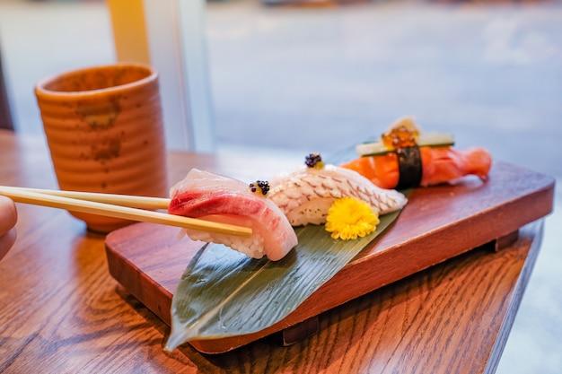 Японская еда, набор суши, поставленный на прямоугольную деревянную тарелку, один кусок палочками и чашку зеленого чая рядом Premium Фотографии