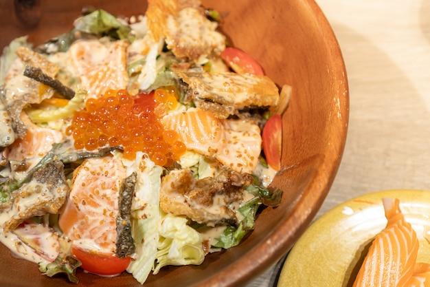 Салат из лосося состоит из различных овощей, свежего лосося, кожицы лосося и икры, подается в деревянной миске Premium Фотографии