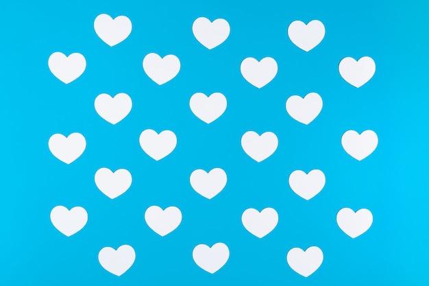 Группа белых сердец на синем фоне Premium Фотографии