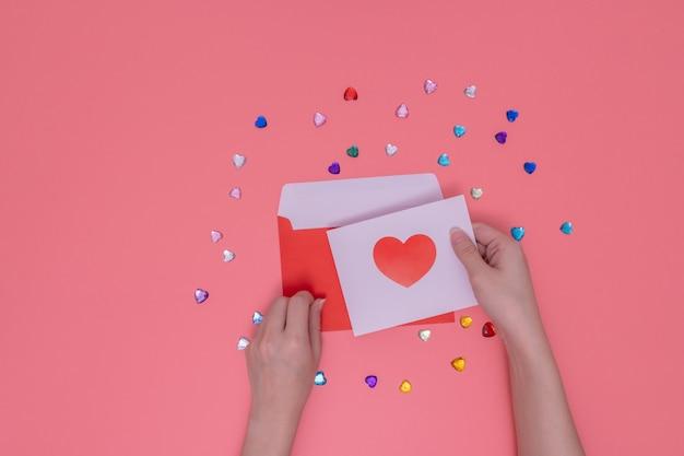 赤い封筒と白い紙に赤いハートを保持している右手。 Premium写真